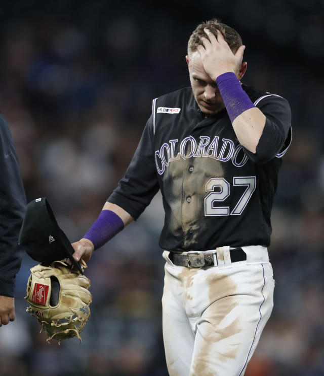 Colorado Rockies shortstop Trevor Story holds his head as he walks off the field after taking to the face a ground-ball single by San Diego Padres' Hunter Renfroe during the eighth inning of a baseball game Friday, June 14, 2019, in Denver. (AP Photo/David Zalubowski)