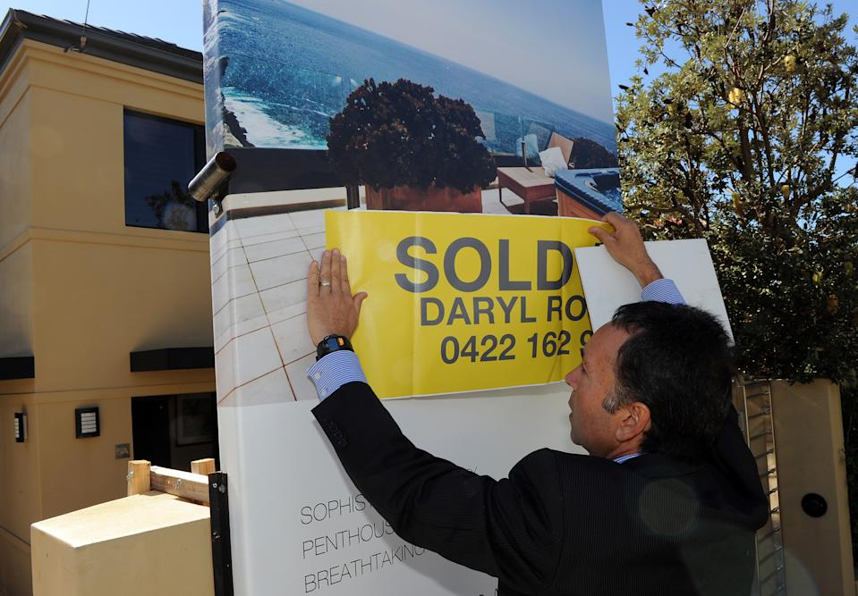 To go with a feature story Australia-property by Madeleine Coorey Eastern suburbs real estate agent Daryl Rosen puts a 'sold' sticker over the advertising signage after another successful multi-million dollar house auction in Sydney on May 8, 2010. In Australia's largest cities of Sydney and Melbourne, the growth in property prices has been enough to ensure many prospective home owners are priced out of the market before they make their first tentative bid.  AFP PHOTO / Torsten BLACKWOOD (Photo credit should read TORSTEN BLACKWOOD/AFP via Getty Images)
