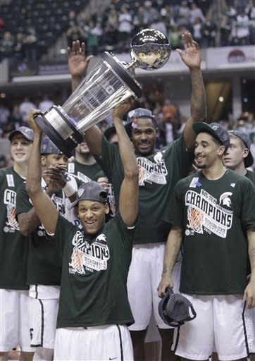 Michigan State center Adreian Payne holds up the Big Ten tournament trophy as he celebrates with teammates after an NCAA college basketball game against Ohio State in tournament final in Indianapolis, Sunday, March 11, 2012. (AP Photo/Michael Conroy)