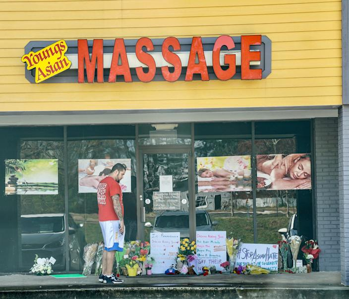 A man looks at the memorial flowers left at Young's Asian Massage in Acworth, Georgia, on Thursday, March 18, 2021, following a shooting.