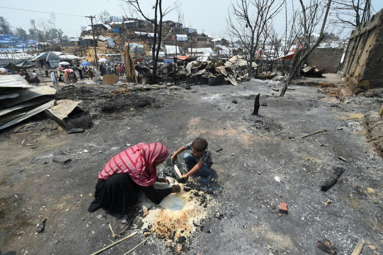 A Rohingya refugee family collects rice which was partially burnt days after a fire at a refugee camp in Ukhia, Bangladesh in March 2021