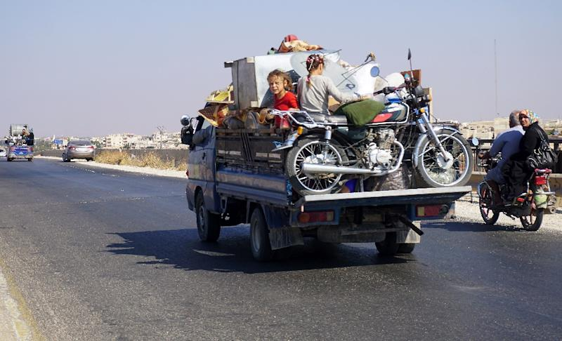 Syrian children squeeze in among family belongings in the back of a pick-up on September 11, 2018 as they flee an anticipated government offensive on Idlib (AFP Photo/Muhammad HAJ KADOUR)