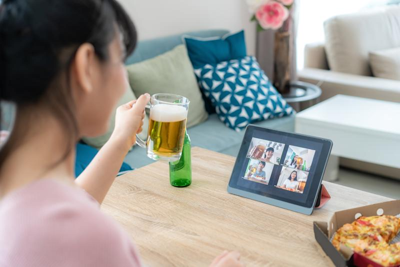 Asian woman virtual happy hour meeting party and drinking alcohol beer online together with her friend in video conference with digital tablet for a online meeting in video call for social distancing for infection risk.