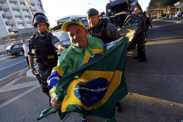 A soccer fan holds a Brazilian flag in front of two policemen outside Ana Rosa subway station during the fifth day of metro worker's protest in Sao Paulo June 9, 2014. A court set a 500,000 reais penalty ($223,000) for each day they stay off work from Monday and also declared the strike illegal, complicating preparations for the World Cup opening match. REUTERS/Kai Pfaffenbach (BRAZIL - Tags: BUSINESS EMPLOYMENT SOCCER SPORT TRANSPORT CIVIL UNREST WORLD CUP)