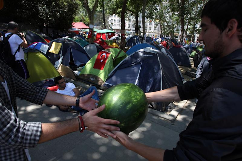 Protesters form a human chain to carry watermelons at the Gezi Park of Taksim Square in Istanbul, Monday, June 10, 2013. Turkey's main opposition party leader Kemal Kilicdaroglu has called on the prime minister Recep Tayyip Erdogan to stop escalating tensions as anti-government protests that have led to three deaths entered their 11th day. (AP Photo/Thanassis Stavrakis)