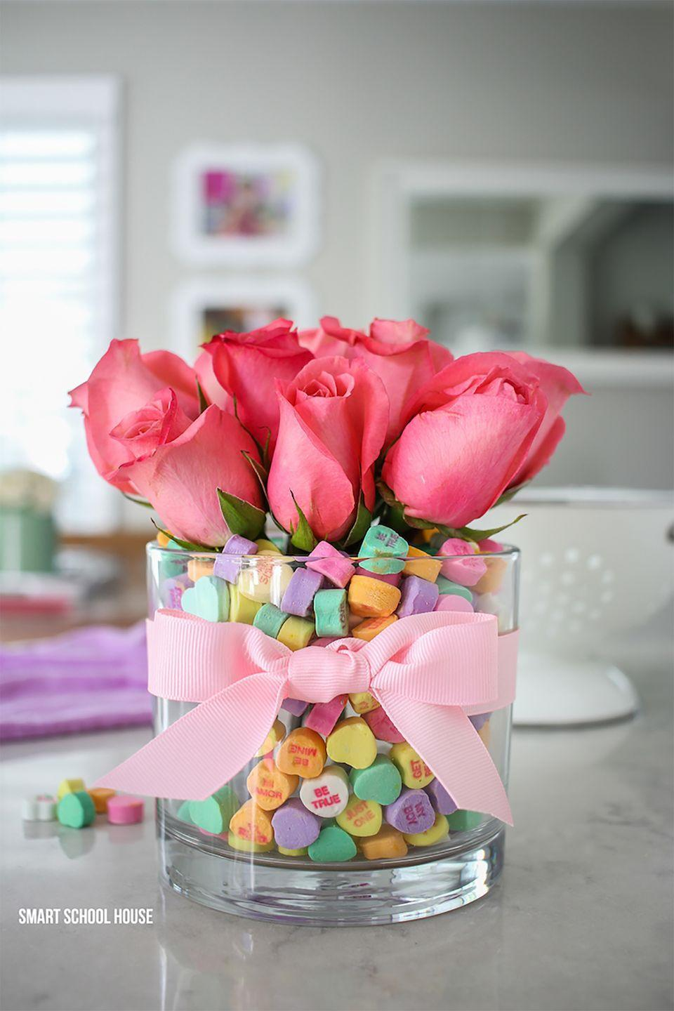 """<p>A vase of water is actually hidden underneath a pile of conversational hearts.</p><p><strong>Get the tutorial at <a href=""""https://www.smartschoolhouse.com/diy-crafts/candy-heart-valentine-bouquet"""" rel=""""nofollow noopener"""" target=""""_blank"""" data-ylk=""""slk:Smart School House"""" class=""""link rapid-noclick-resp"""">Smart School House</a>.</strong></p><p><strong><a class=""""link rapid-noclick-resp"""" href=""""https://www.amazon.com/b?ie=UTF8&node=16091540011&tag=syn-yahoo-20&ascsubtag=%5Bartid%7C10050.g.2971%5Bsrc%7Cyahoo-us"""" rel=""""nofollow noopener"""" target=""""_blank"""" data-ylk=""""slk:SHOP GLASS VASES"""">SHOP GLASS VASES</a><br></strong></p>"""