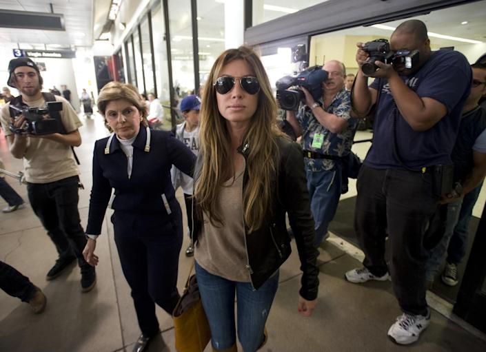 Rachel Uchitel is surrounded by paparazzi at LAX in 2009 alongside her lawyer, Gloria Allred.