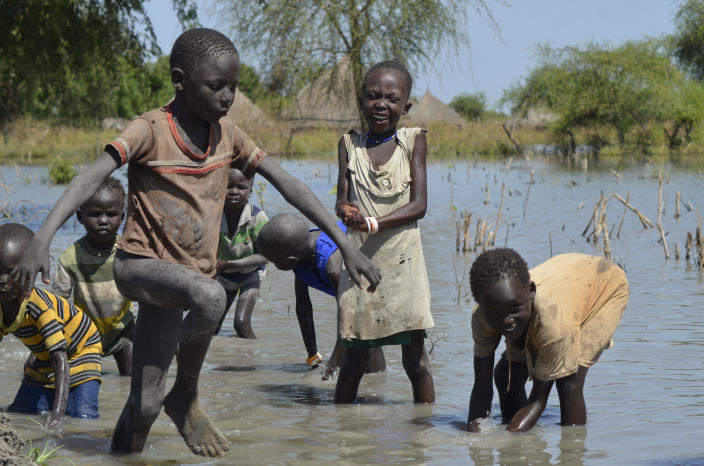 Children wash themselves in muddy floodwaters in the village of Wang Chot, Old Fangak county, Jonglei state, South Sudan Thursday, Nov. 26, 2020. Some 1 million people in the country have been displaced or isolated for months by the worst flooding in memory, with the intense rainy season a sign of climate change. (AP Photo/Maura Ajak)