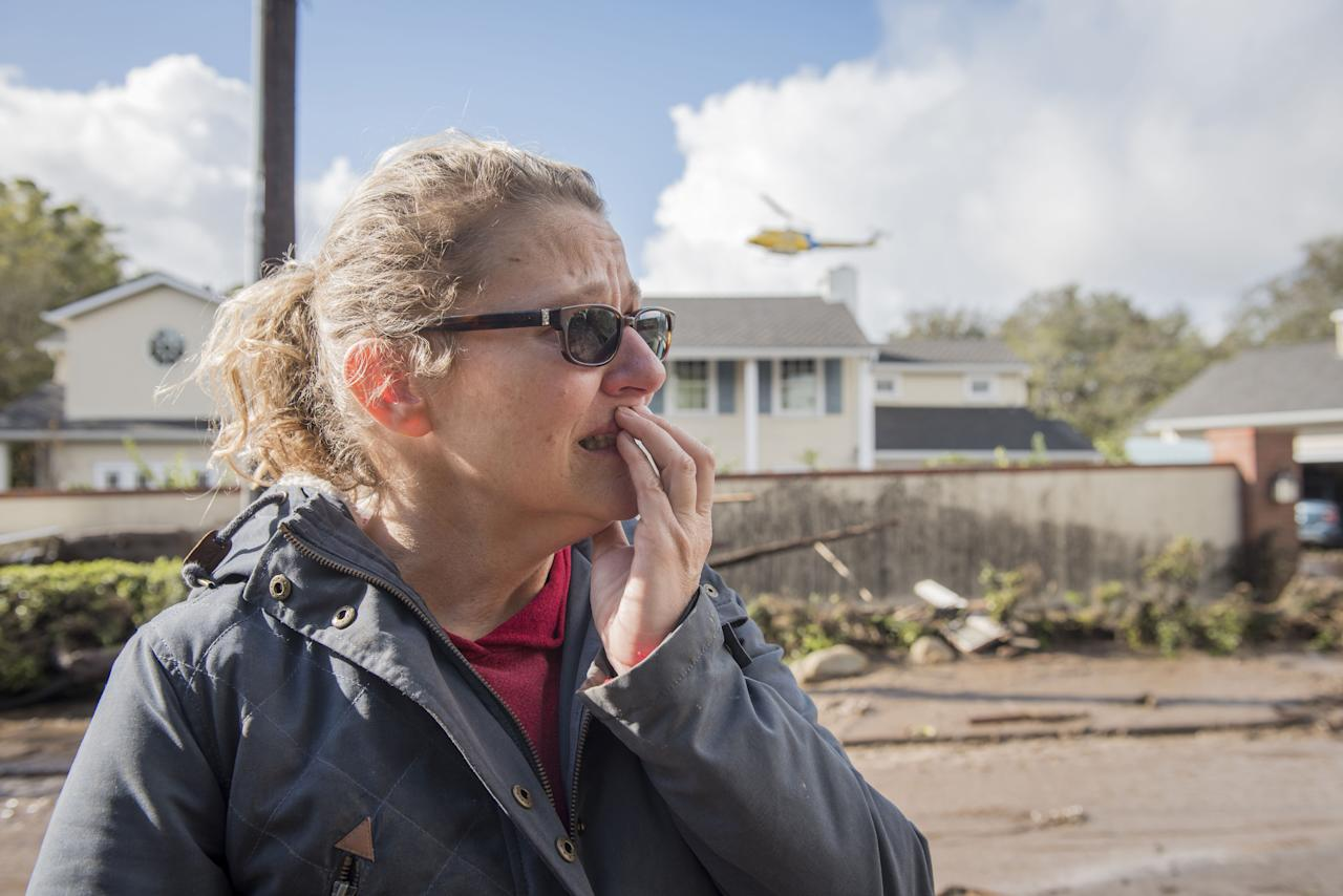 <p>Sara Wilcox looks at the damage done by a mudslide on Olive Mill Rd in Montecito, Calif., on Jan.9, 2018. (Photo: Erick Madrid via ZUMA Wire) </p>