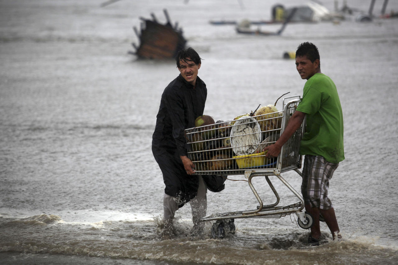 Coconut vendors try to recover their goods after they were caught unprepared when high waves dragged their beach stalls into the sea in Veracruz, Mexico, Thursday, Aug. 9, 2012. Tropical Storm Ernesto headed into Mexico's southern Gulf coast as authorities in the flood-prone region prepared shelters, army troops and rescue personnel for drenching rains. (AP Photo/Felix Marquez)