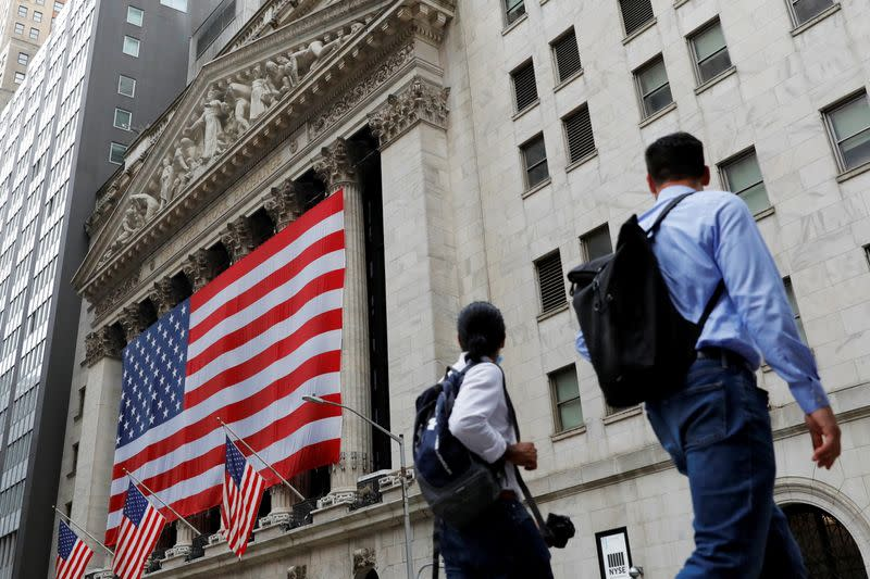 FILE PHOTO: People walk by the New York Stock Exchange (NYSE) in Manhattan, New York City