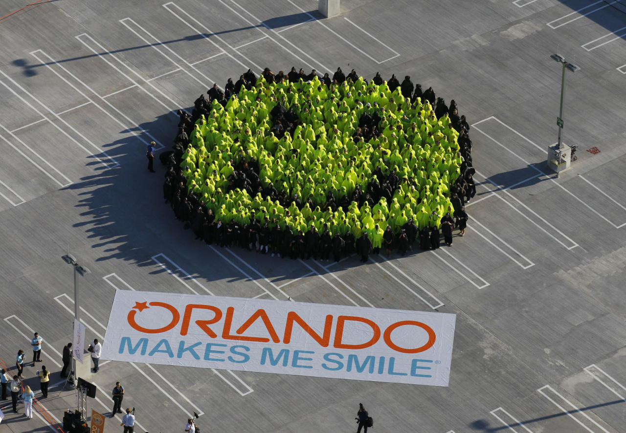 In this publicity image released by the Orlando Convention & Visitors Bureau, five hundred people gather to set a new Guinness World Record for the world's largest smiley face on World Smile Day in Orlando, on Friday, Oct. 1, 2010. (AP Photo/Orlando CVB, Rick Fowler)