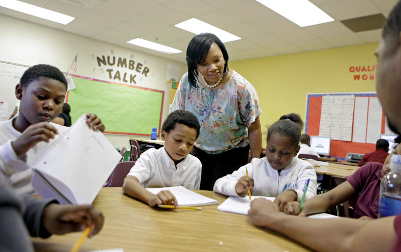 FILE - In this April 18, 2013, file photo, Burgess-Peterson Elementary School principal Robin Robbins, center, meets with students during an after-school study program in Atlanta, in preparation for state standardized testing, soon to begin. A new poll from the Associated Press-NORC Center for Public Affairs Research finds parents of school-age children view standardized tests as a useful way to track student progress and school quality. Most parents say their own children are given about the right number of standardized tests, according to the AP-NORC poll. And almost three quarters say they favor changes that would make it easier for schools to fire poorly performing teachers. (AP Photo/David Goldman)