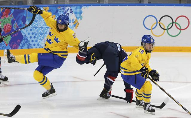 Sweden's Emilia Andersson (L) and Team USA's Hilary Knight collide with Sweden's Pernilla Winberg (R) during the first period of their women's ice hockey semi-final game at the Sochi 2014 Winter Olympic Games February 17, 2014. REUTERS/Grigory Dukor (RUSSIA - Tags: SPORT ICE HOCKEY OLYMPICS)