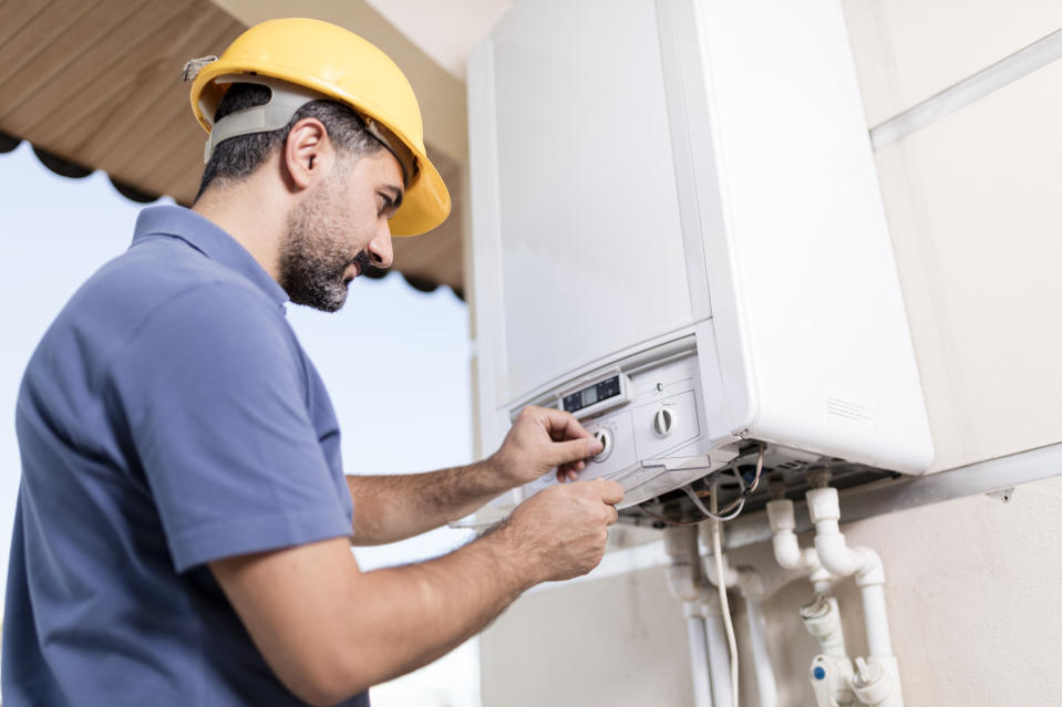 Boiler technician working in home.