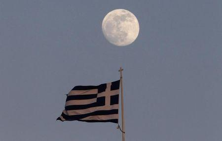 A Greek flag flutters on the top of the parliament as the moon rises in Athens May 23, 2013. REUTERS/John Kolesidis