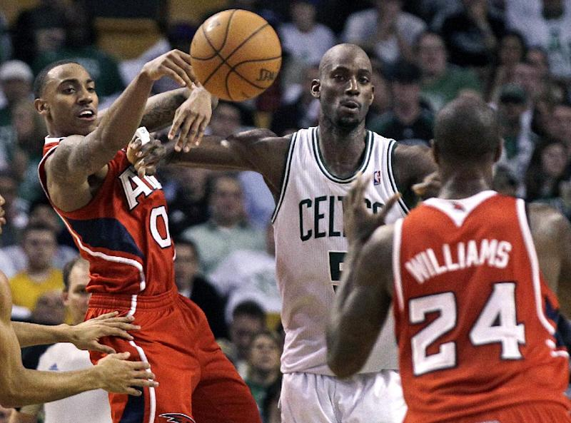 Atlanta Hawks guard Jeff Teague (0) passes off to teammate Marvin Williams (24) against Boston Celtics' Kevin Garnett, center, during the second quarter of Game 3 of an NBA first-round playoff basketball series, Friday, May 4, 2012, in Boston. (AP Photo/Charles Krupa)