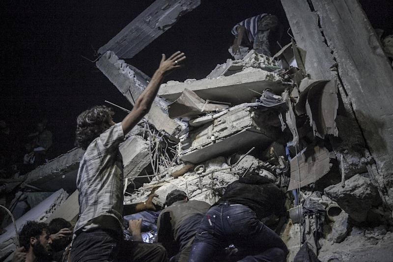 In this Sunday, Sept. 22, 2013 photo, Syrian villagers remove debris as they try to rescue victims, not pictured, of a building destroyed due to an airstrike that hit a village turned into a battlefield between government forces and Free Syrian Army fighters in Idlib province, northern Syria. (AP Photo)
