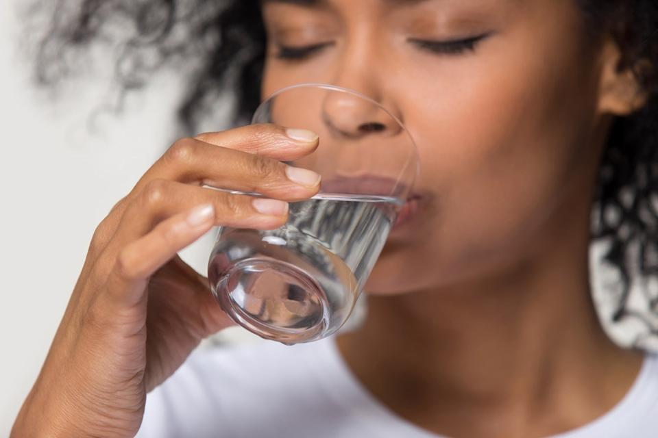 Close up focus on female hand holding glass african woman drinking still water