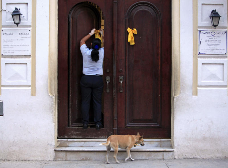 Miladys Ramirez, who works as a security officer, puts a yellow ribbon on the door of a state building to commemorate the 15th anniversary of the arrest in the U.S. of five Cuban agents, known as the Cuban Five, in Havana, Cuba, Thursday, Sept. 12, 2013. Rene Gonzalez, one of the five who was freed in 2011, called for people to wear and hang yellow ribbons to press for the release of the four others still in U.S. prisons. (AP Photo/Franklin Reyes)