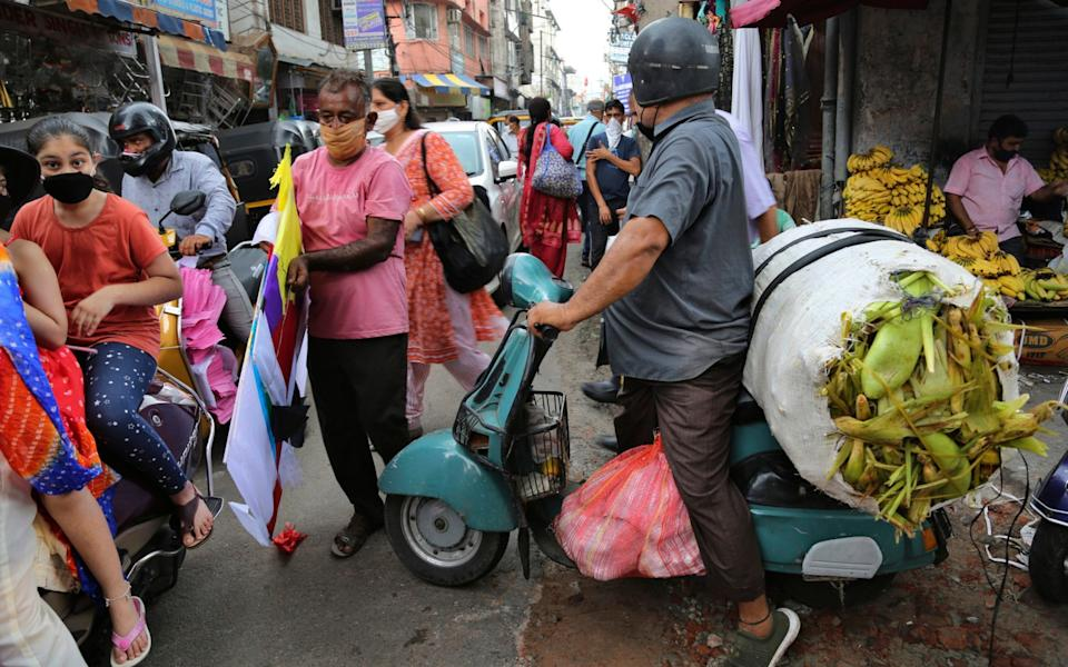 Indians wearing face masks as a precaution against the coronavirus walk at a market in Jammu, India - Channi Anand / AP