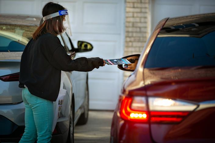 A woman in mask and face shield hands a pamphlet to a person in a car.