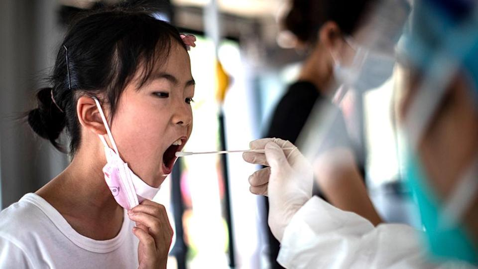 A medical worker takes samples during a mass Covid-19 test in a residential block on August 3, 2021 in Wuhan