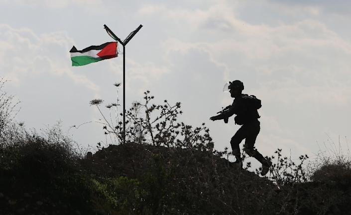 A member of the Israeli security forces runs past a Palestinian flag during clashes with Palestinian stone throwers in the West Bank town of Tulkarem on November 10, 2015 (AFP Photo/Jaafar Ashtiyeh)