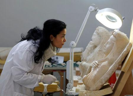 A specialist works on a damaged statue from Palmyra at Syria's National Museum of Damascus