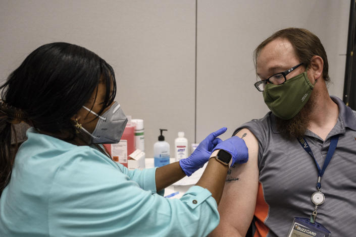FILE - In this Thursday, April 8, 2021 file photo, Georgia Tech employee Adam Jackson receives a Pfizer COVID-19 vaccination at the Vaccination Site on the campus of Georgia Tech in Atlanta. The University System of Georgia announced Thursday, May 13, 2021 that students and employees will not be required to be vaccinated for the start of the fall 2021 semester.. (AP Photo/Danny Karnik, File)