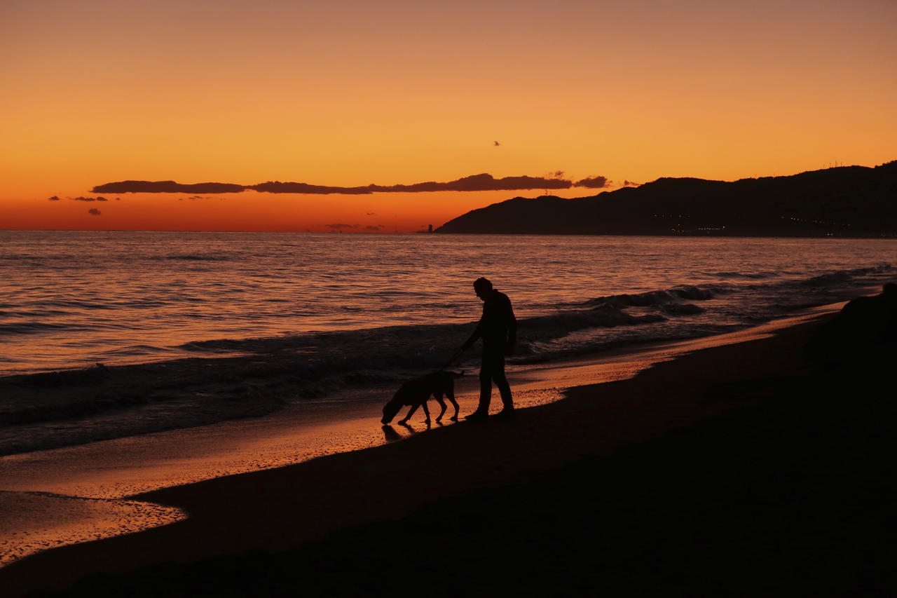 <p>A man walks with his dog along the beach during the last moments of the sunset in Castelldefels, Spain, Sunday, Nov 12, 2017. (AP Photo/Manu Fernandez) </p>