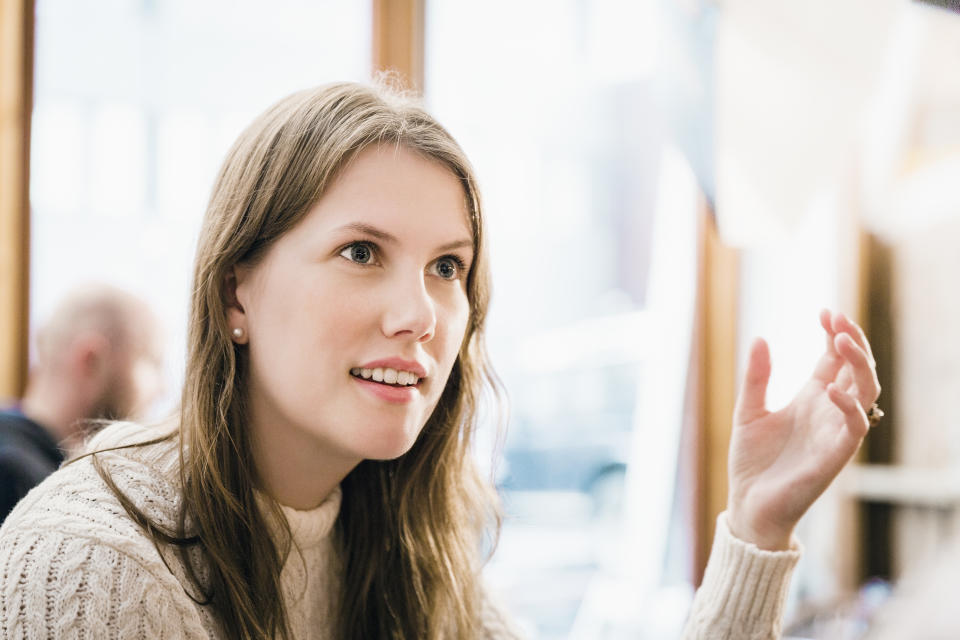 Shocked young woman gesturing while looking away at restaurant