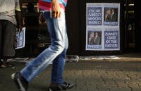 """A man walks past posters of newspapers with a headline that refers to South African """"Blade Runner"""" Oscar Pistorius at a newspaper stall outside court in Pretoria February 15, 2013. Pistorius, a double amputee who became one of the biggest names in world athletics, broke down in tears on Friday after he was charged in court with shooting dead his girlfriend, model Reeva Steenkamp, in his Pretoria house. REUTERS/Siphiwe Sibeko (SOUTH AFRICA - Tags: CRIME LAW SPORT ATHLETICS OLYMPICS)"""