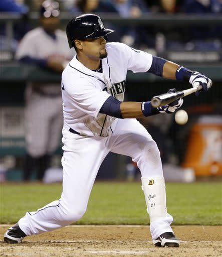 Seattle Mariners' Franklin Gutierrez bunts in a run against the Houston Astros in the fifth inning of a baseball game, Monday, April 8, 2013, in Seattle. (AP Photo/Elaine Thompson)