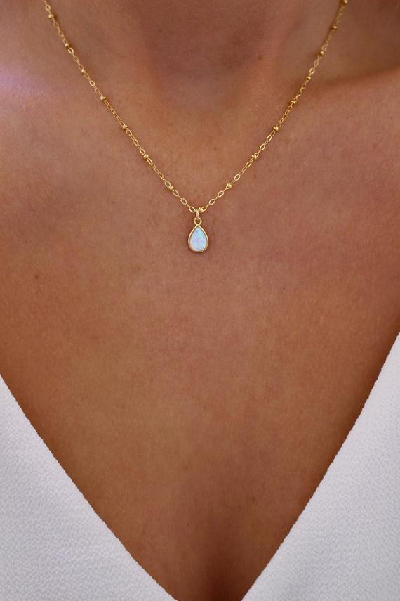"""<h2>October: Opal</h2><br>This unique milky gem repels negative energy. """"Because of all its different colors, it can activate each one of the seven chakras as well as infuse the aura with a full spectrum of light,"""" Montúfar explains.<br><br><strong>ShopErinMichele</strong> Opal Pendant, $, available at <a href=""""https://www.etsy.com/listing/728441510/opal-pendant-gold-opal-necklace-dainty"""" rel=""""nofollow noopener"""" target=""""_blank"""" data-ylk=""""slk:Etsy"""" class=""""link rapid-noclick-resp"""">Etsy</a>"""
