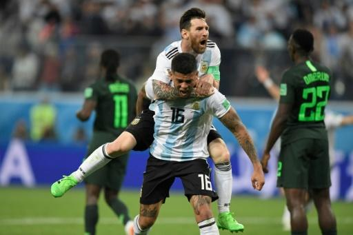 Lionel Messi leaps on Marcos Rojo's shoulders in joy