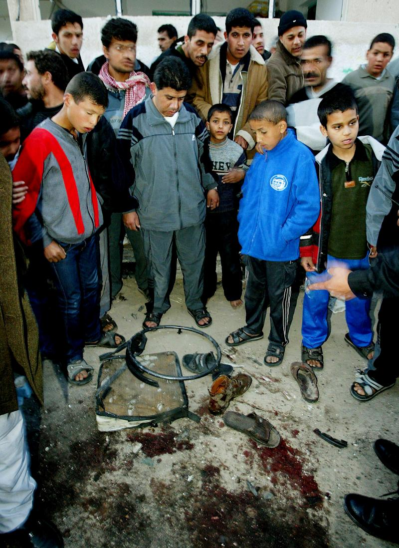 FILE - In this March 22, 2004, file photo, Palestinians gather around a pool of blood and the remains of the wheelchair of Hamas spiritual leader Sheikh Ahmed Yassin, following an Israeli air strike that killed him, near his house in Gaza City. Israel is considering resuming its contentious practice of assassinating militant leaders in the Hamas-ruled Gaza Strip in an effort to halt intensified rocket attacks on Israel's south, according to defense officials.  (AP Photo/Kevin Frayer, File)