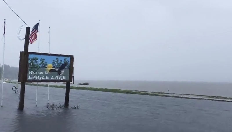 "This Sunday, July 14, 2019, image made from a cellphone video provided by the Mississippi Governor's Office shows the flooded welcome sign at the entrance to Eagle Lake community near Vicksburg, Miss. In a Monday, July 15, posting of the short video on Twitter, Gov. Phil Bryant made reference that ""the South Delta has become an ocean,"" with the additional rainfall from Tropical Depression Barry, while calling on the federal government to build pumps to drain water from the confluence of the Yazoo and Mississippi Rivers. (Bobby Morgan/Office of Mississippi Gov. Phil Bryant via AP)"