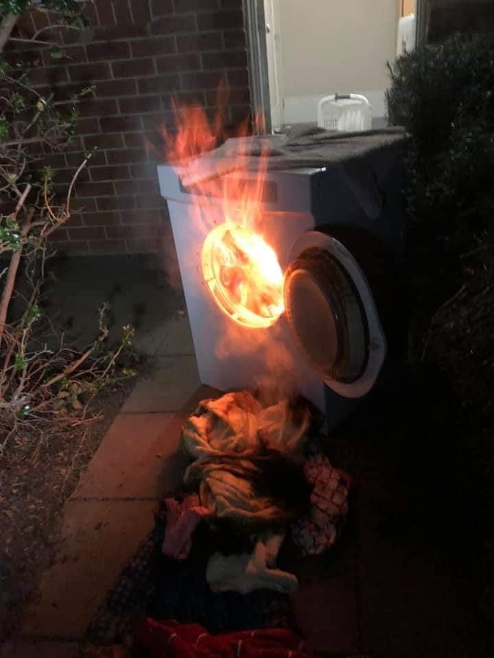 Flames protrude out of the door of a dryer on fire at a Murrumbateman home.