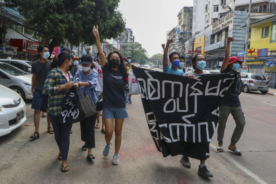 Anti-coup protesters shout slogan with a banner reading ''Carry on revolution! We do not accept as the military slave,'' in Kamayut township of Yangon, Myanmar, Monday, April 19, 2021. Anti-coup protesters kept public demonstrations going despite the threat of lethal violence from security forces. (AP Photo)