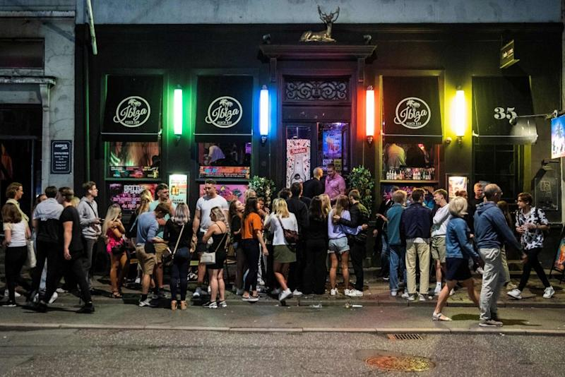 Revellers outside a bar in Copenhagen following the announcement of a curfew for social venues - getty
