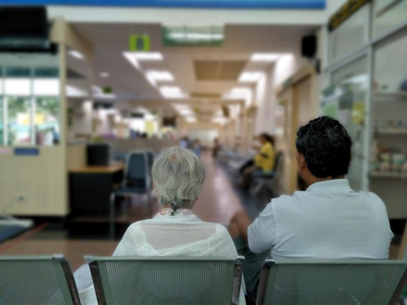 old woman and adult man sit on gray stainless chair waiting medical and health services to the hospital,patients waiting treatment