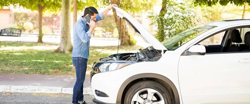 Young man standing in front of his broken car, looking at car engine and talking on cell phone