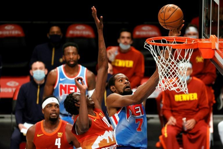 Brooklyn's Kevin Durant shoots as Denver's Bol Bol and Paul Millsap defend in the Nets' 122-116 NBA victory over the Nuggets