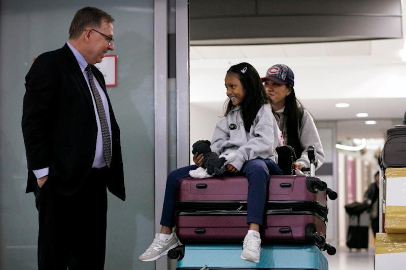 Lawyer Robert Tibbo greets Vanessa Rodel and her daughter Keana as the pair arrive in Canada at the Toronto airport on a flight from Hong Kong on March 25, 2019 (AFP Photo/Cole BURSTON)