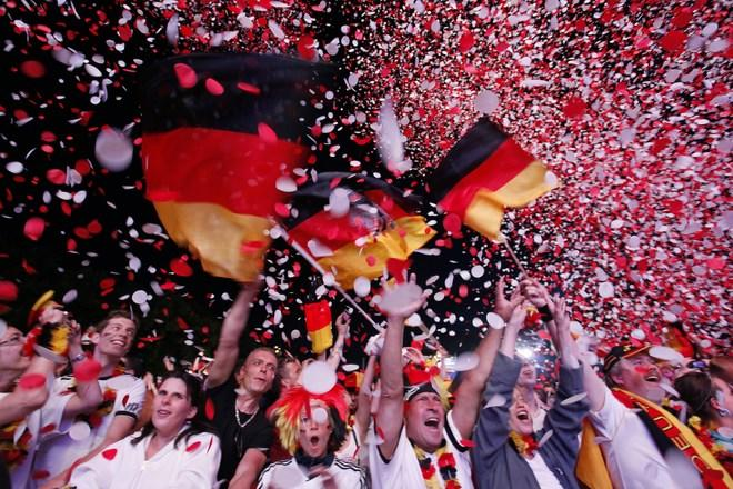 "TOPSHOTS Supporters of the German national football team cheer with German flags at the end of the public screening of Germany's opening match in the UEFA Euro 2012 against Portugal at the ""Fanmeile"" (Fan Mile) in Berlin on June 9, 2012.  Germany won 1:0 against Portugal. AFP PHOTO / MICHELE TANTUSSIMICHELE TANTUSSI/AFP/GettyImages"