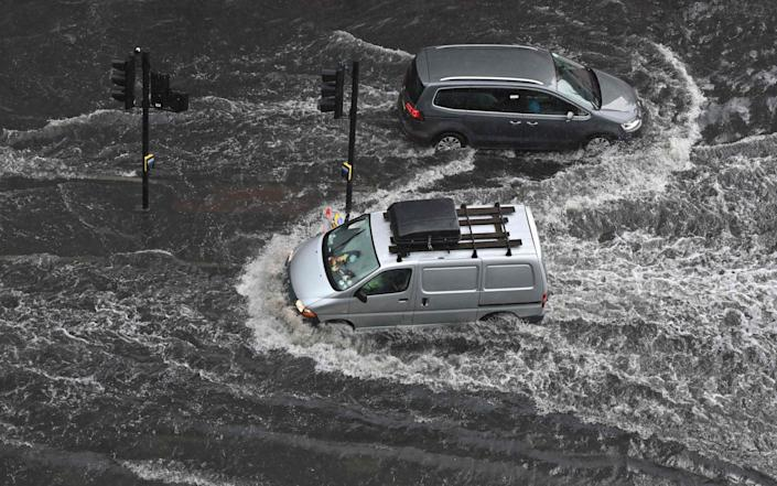 Vehicles drive through deep water on a flooded road in The Nine Elms district of London - JUSTIN TALLIS
