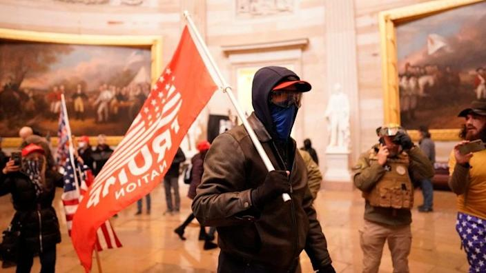 Rioter in the capitol rotunda with Trump flag