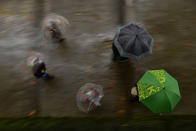 Pedestrian keep save a distance while sheltering from the rain under umbrellas, during an autumn day, in Pamplona, northern Spain, Saturday, Oct. 3, 2020. (AP Photo/Alvaro Barrientos)