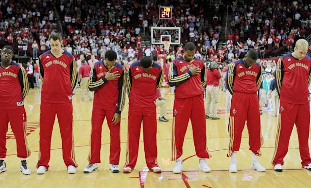New Orleans Pelicans players line up in their new uniform warmups during the national anthem before a preseason NBA basketball game against the Houston Rockets in Houston, Saturday, Oct. 5, 2013. (AP Photo/Richard Carson)